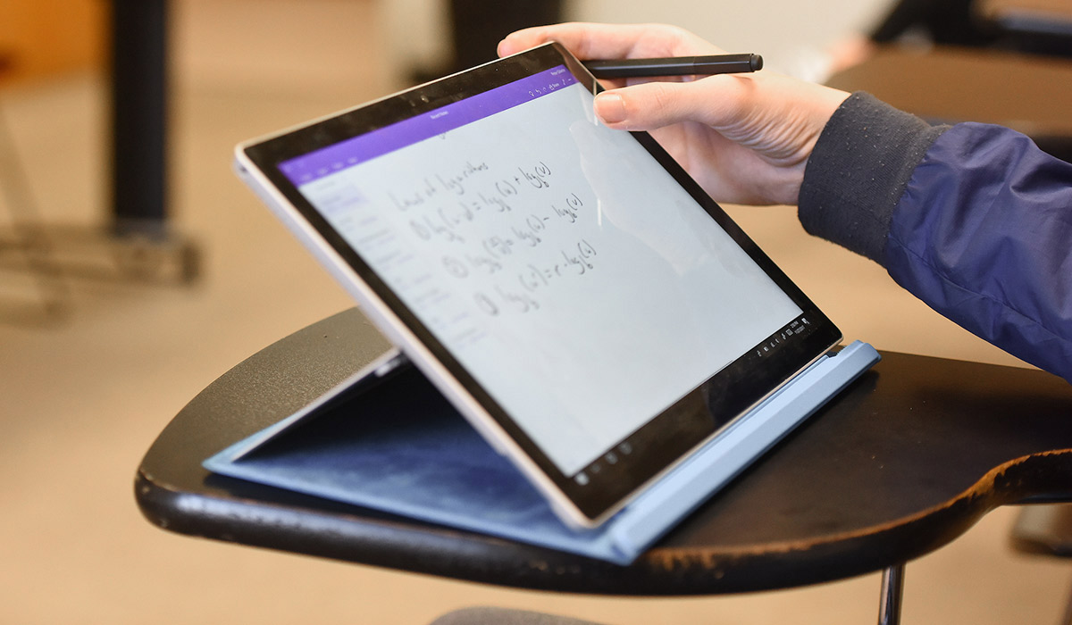 Student taking notes on a tablet
